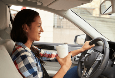 Smiling woman sitting in car holding coffee cup