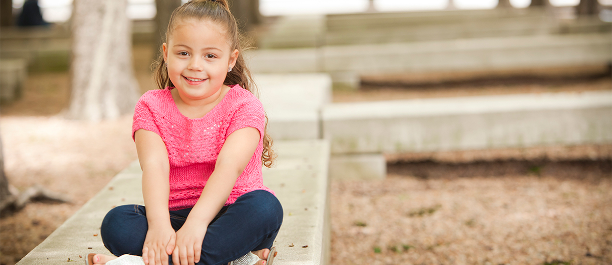 Young girl sitting outside at park with legs crossed