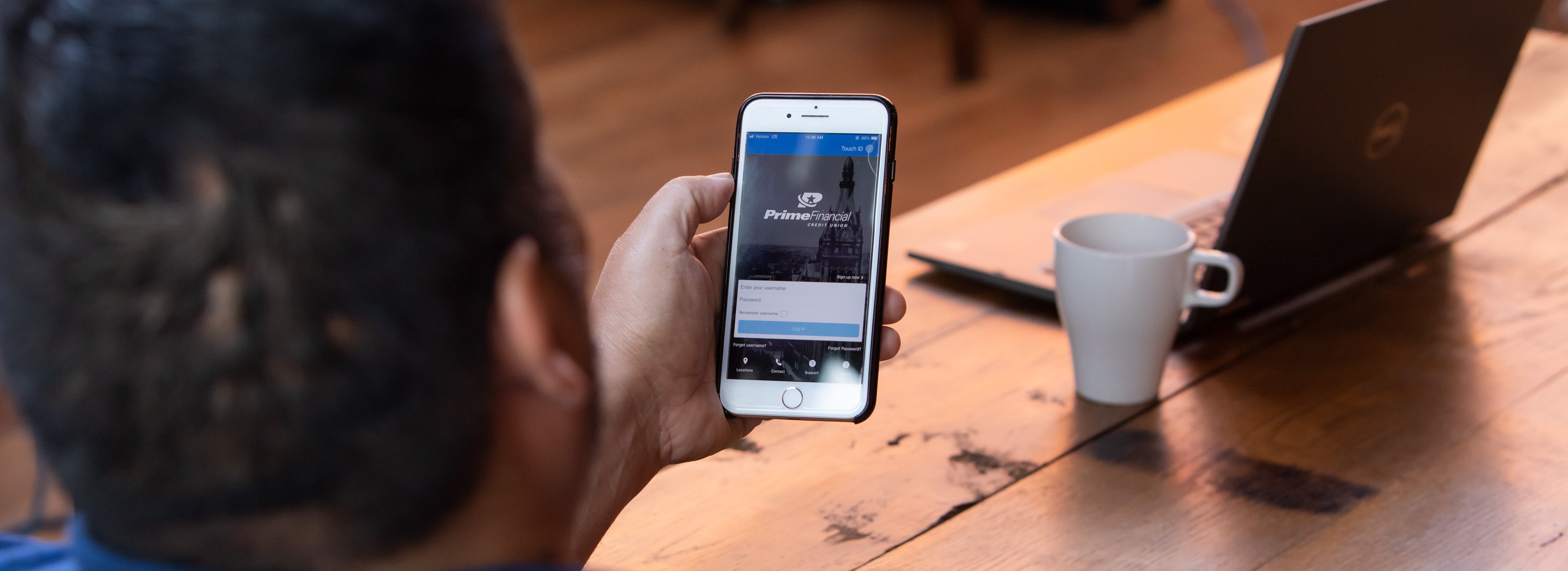 Man using mobile banking app on phone at cafe