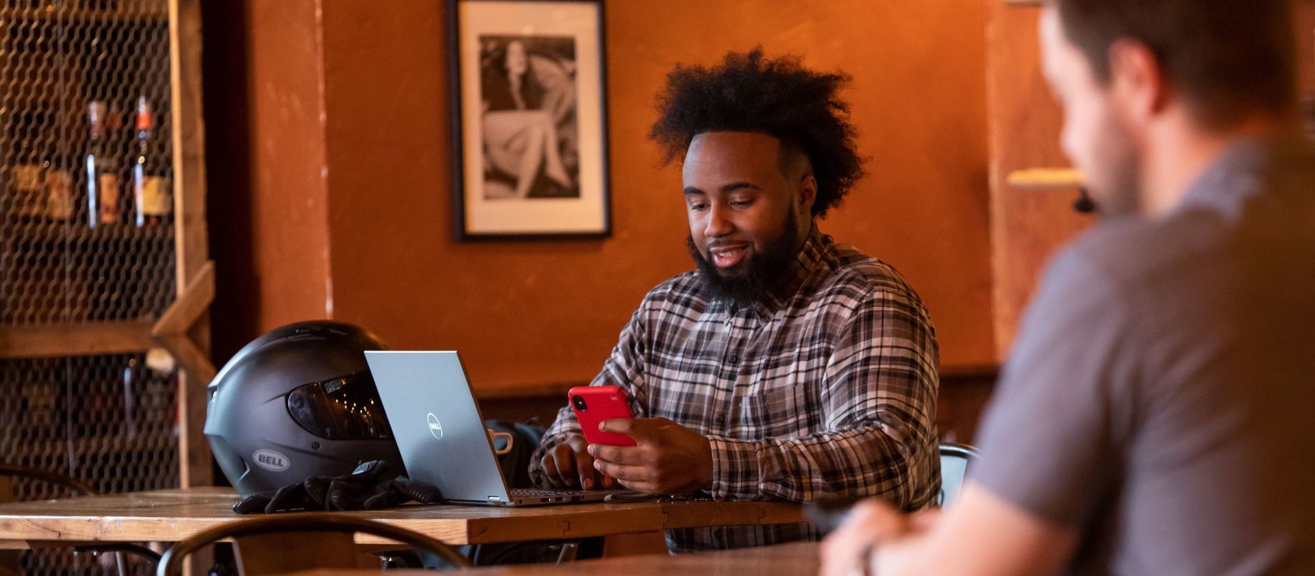 Man using phone while sitting by laptop in cafe