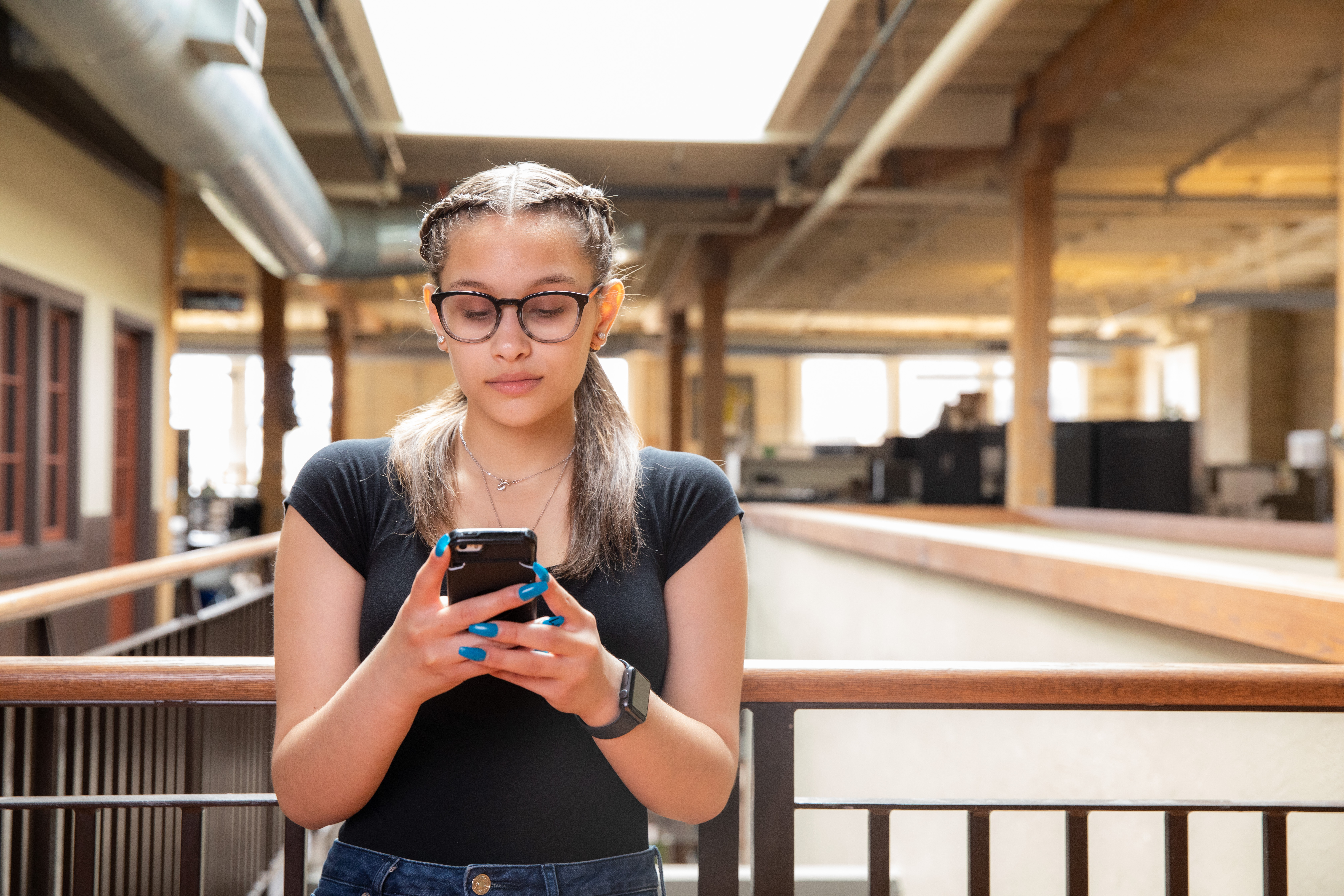 Teen girl using phone while leaning against railing